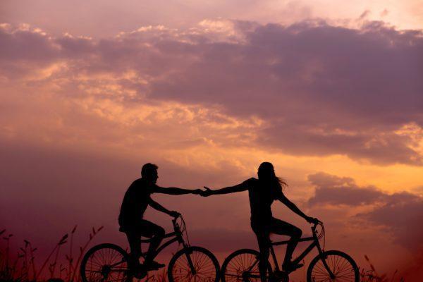 Girl helping a boy in cycling