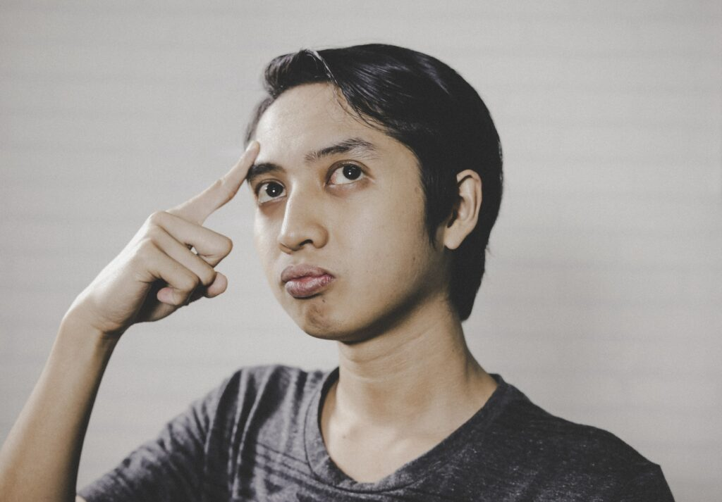 A young woman places index finger on forehead and looks to the upper left quadrant of her vision. She is deep in thought and looks perplexed.